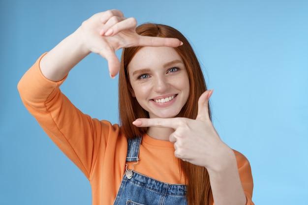 Creatieve knap mooie roodharige vrouwelijke assistent zoekt inspiratie laat hand frame kijken door opgetogen glimlachen tevreden gevonden geweldige plek nemen shot staande blauwe achtergrond