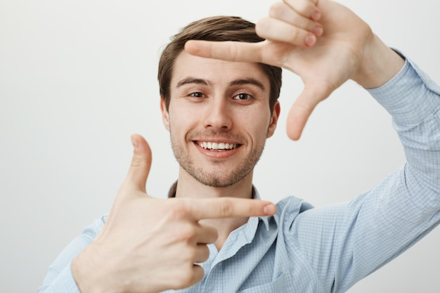 Creatieve knappe man glimlachend, hand frames tonen, moment vastleggen