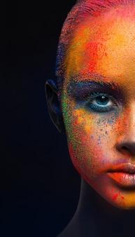 Creatieve kunst make-up, de helft van het vrouwelijk gezicht. holi-kleuren. portret van jonge mode-model met heldere kleurrijke mix van verf op haar gezicht