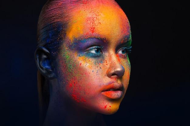 Creatieve kunst make-up. portret van model met heldere, kleurrijke mix van verf op haar gezicht. kleurfantasie, artistieke make-up.
