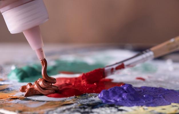Creatieve kunstenaar die penseel gebruikt om groene en rode olieverf op kleurrijk palet te mengen.