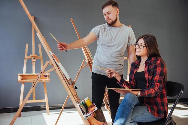 Creatieve kunstenaars schilderen een kleurrijk beeld op canvas met olieverf