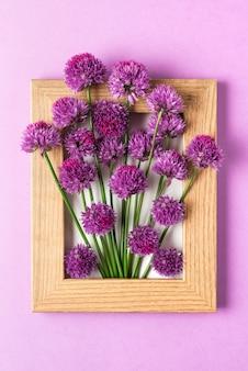 Creatieve lay-out gemaakt met paarse bloemen in fotolijst op paars. plat liggen. bloemsamenstelling