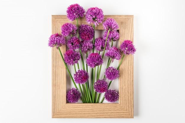 Creatieve lay-out gemaakt met paarse bloemen in fotolijst op wit. plat liggen. bloemsamenstelling