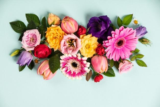 Creatieve lay-out gemaakt met prachtige bloemen op blauwe achtergrond. plat leggen. lente minimaal concept
