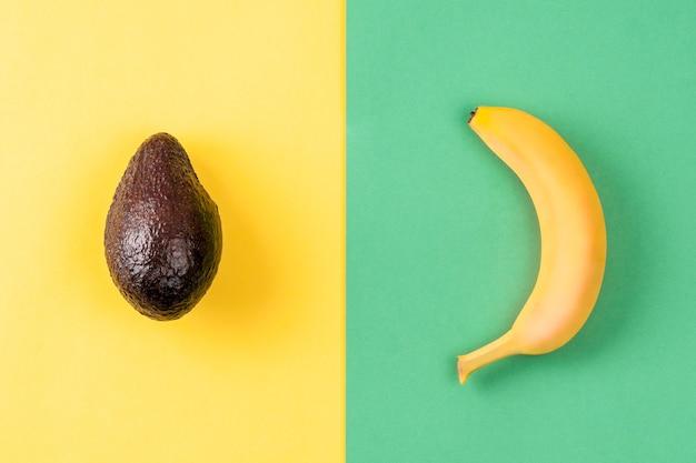 Creatieve lay-out gemaakt van banaan en avocado op kleurrijke groene en gele achtergrond. minimaal zomerconcept. vruchten ontwerp.