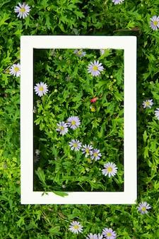 Creatieve lay-out gemaakt van bloemen en bladeren met wit frame. bovenaanzicht. natuur concept