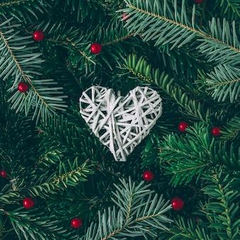 Creatieve lay-out gemaakt van kerstboomtakken met hartdecoratie. plat leggen. natuur nieuwjaar concept.