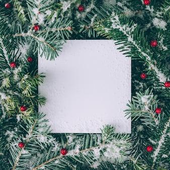 Creatieve lay-out gemaakt van kerstboomtakken met sneeuw en papieren kaartnota. plat leggen. natuur nieuwjaar concept.