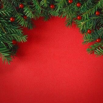 Creatieve lay-out gemaakt van kerstboomtakken op rode achtergrond. plat leggen. natuur kerst concept