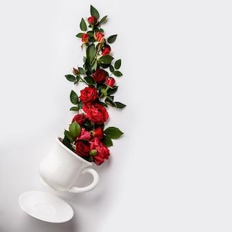 Creatieve lay-out gemaakt van koffie of thee beker met rode rozen op witte achtergrond