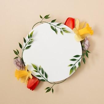 Creatieve lay-out gemaakt van lente bladeren en bloemen met witte cirkel kopie ruimte