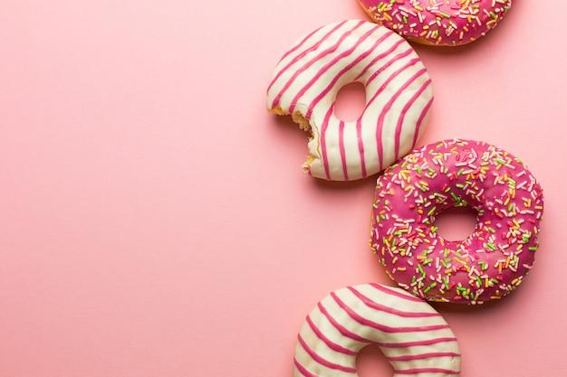Creatieve lay-out gemaakt van roze geglazuurde donuts