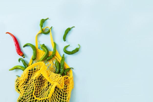 Creatieve lay-out groene chili pepers. groene groenten in gele string zak op pastel blauwe achtergrond. hoop groene peper genaamd frigitelli