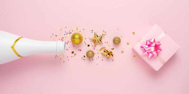 Creatieve lay-out met champagnefles, geschenkdoos en gouden glitterdecoratie.