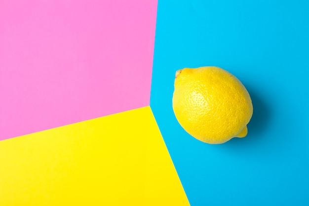 Creatieve lay-out met gele citroen en kleurrijke levendige papieren. abstracte kleuren kunst achtergrond. minimaal fruitconcept. plat leggen.