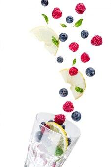 Creatieve lay-out met verse bessen, eenvoudig patroon. frambozen, bosbessen, muntblaadjes, plakjes citroen. concept een mojito van de de zomerdrank, limonade, met een glas.