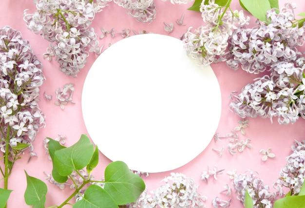 Creatieve lay-out van lila bloemen met wit papier. mockup. uitzicht van boven.