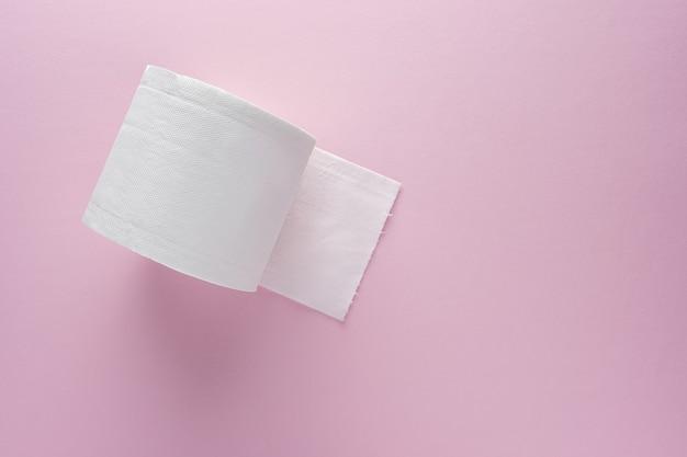 Creatieve lay-out van wc-papierrol op roze achtergrond.