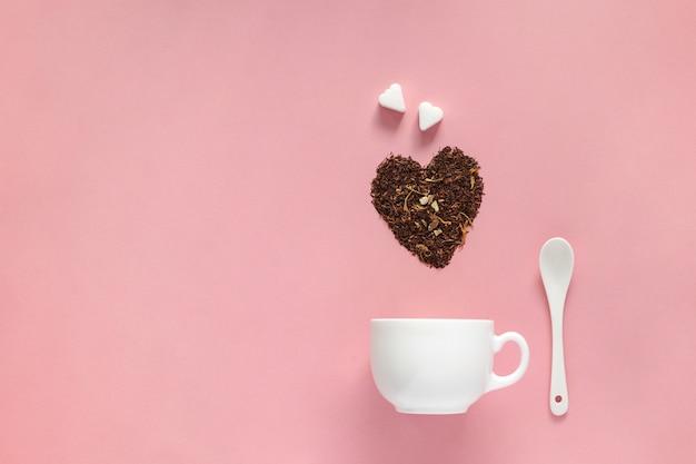 Creatieve lay-out van witte kop met vorm van hart droge bloemen groene thee en suiker op roze achtergrond