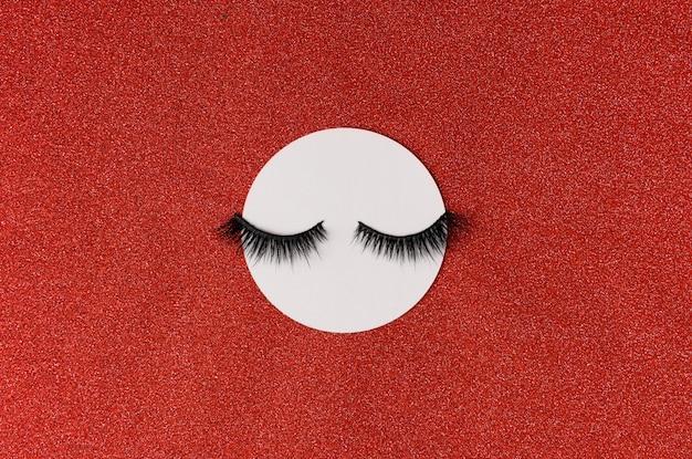 Creatieve layout met wimpers. gesloten ogen op rode sprankelende achtergrond
