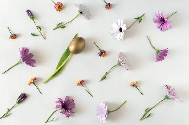 Creatieve lente lay-out gemaakt van kleurrijke bloemen en gouden ei op witte achtergrond