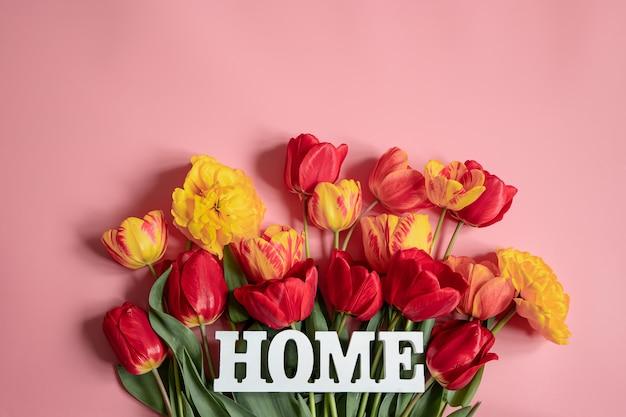 Creatieve lentecompositie met bloemen verspreid over het oppervlak en het woord thuis.