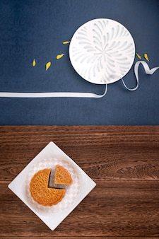 Creatieve maancake mooncake-ontwerpinspiratie, geniet van de maan in het midden van de herfstfestival met gebak en thee op houten tafelconcept, bovenaanzicht, plat gelegd