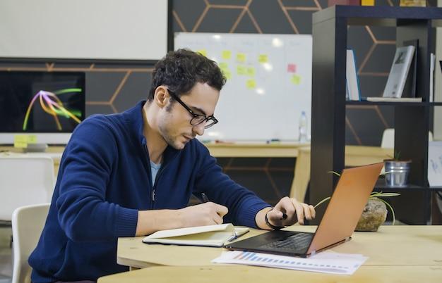 Creatieve man die aantekeningen maakt op zijn werkplek in een helder modern kantoor
