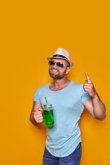 Creatieve man in zonnebrillen en zomerkleren stijlvolle hoed die ontspannen staat en drinkt van creati...