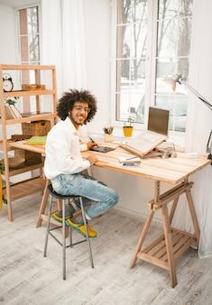 Creatieve mens die met laptop thuis bureaubinnenland werken