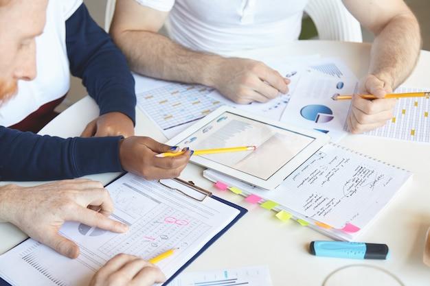 Creatieve mensen van verschillende etnische groepen die samen aan een businessplan werken, de groeisnelheid, de waarde van goederen en diensten analyseren, de markt bestuderen, het verlies tellen, de touchpad-pc gebruiken en aantekeningen maken