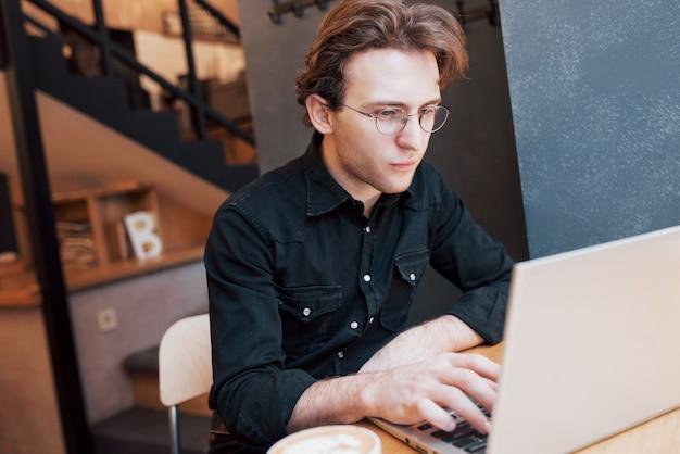 Creatieve mensenontwerper die aan zijn laptop computer tijdens ochtendontbijt werken in het moderne binnenland van de koffiewinkel
