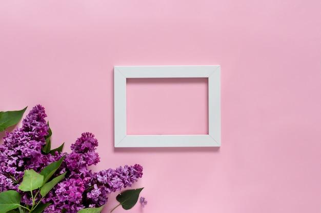 Creatieve minimalistische banner met lila bloemen en wit frame op trendy roze achtergrond. webbanner. bovenaanzicht, plat lag, kopieer ruimte.