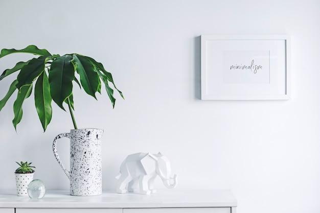 Creatieve minimalistische woonkamer interieur met mock up poster frame witte moderne commode groen blad in creatief ontworpen vaas plant in hipster pot en sculptuur van olifant witte muren sjabloon