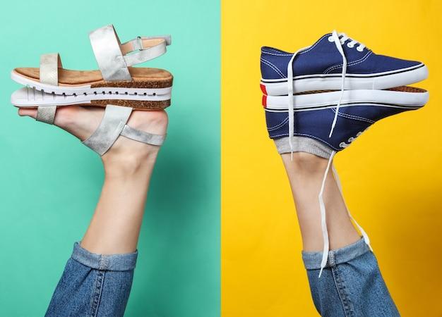Creatieve mode-opname. hipster sneakers en sandalen op de hiel van de verhoogde vrouwelijke benen op geelblauw.