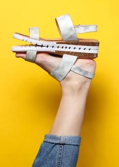Creatieve mode-opname. modieuze damessandaal op de hiel van het verhoogde vrouwelijke been op geel.