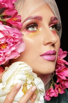 Creatieve mode schoonheid portret van mooie jonge vrouw met bloem make-up