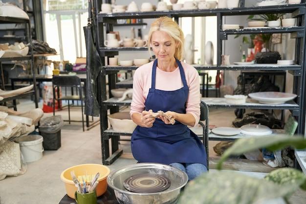 Creatieve momenten portret van gelukkige vrouw in blauwe schort maken van handgemaakte klei keramiek in aardewerk