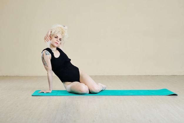 Creatieve mooie fit jonge danseres rustend op yogamat en na te denken over nieuwe dansbeweging
