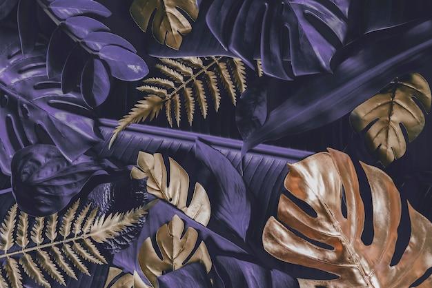 Creatieve natuurachtergrond goud en paars tropische monstera en palmbladeren