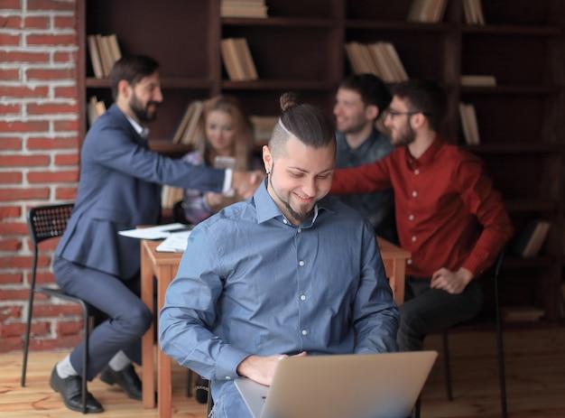 Creatieve ontwerper die aan een laptopfoto aan de handdruk van zakenpartners werkt