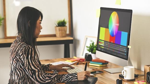 Creatieve ontwerperzitting bij houten bureau die digitale tablet gebruiken voor het selecteren van kleur