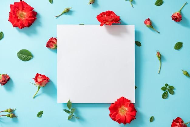 Creatieve opstelling van rode bloemen en bladeren op pastelblauw met papieren kaartnota.