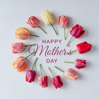 Creatieve opstelling van tulpen op witte muur met gelukkige moederdagtekst. plat leggen.