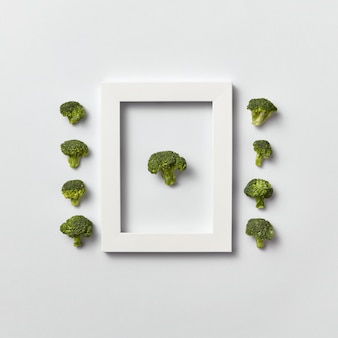 Creatieve organische compositie met vers geplukte groene broccoli in een frame en eruit op een lichtgrijze muur, plaats voor tekst. plat leggen. veganistisch concept.