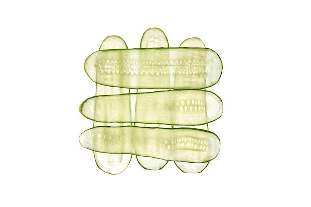Creatieve patroon van dunne plakjes verse natuurlijke biologische komkommergroente op een witte tafel, kopie ruimte. bovenaanzicht.