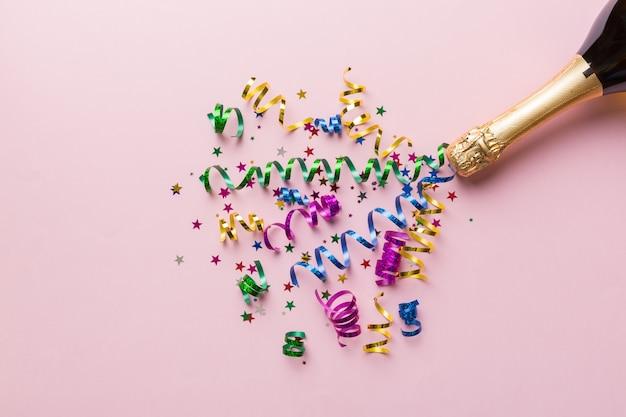 Creatieve plat lag compositie met fles champagne en ruimte voor tekst op kleur achtergrond. champagnefles met kleurrijke feestwimpels. vakantie of kerst concept