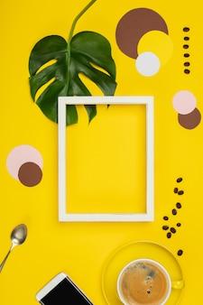 Creatieve plat lag met een kopje koffie, tropische planten en fotolijstjes