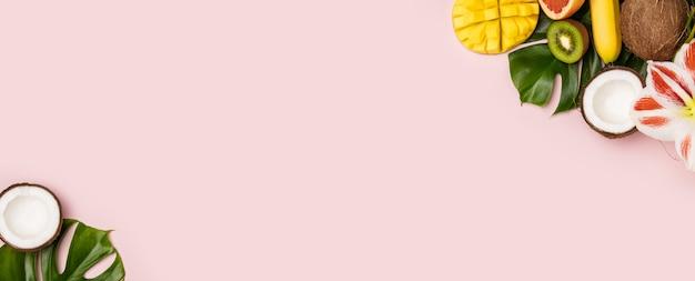 Creatieve plat lag met tropische vruchten en planten op roze achtergrond